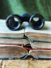 vintage-binoculars-on-stack-of-open-books-jill-battaglia